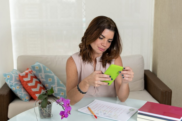 Rijpe vrouw die bij haar thuiskantoor werkt en een bericht op haar smartphone schrijft.