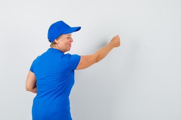Rijpe vrouw die doet alsof ze op de deur klopt in een blauw t-shirt en opgewonden kijkt, achteraanzicht.