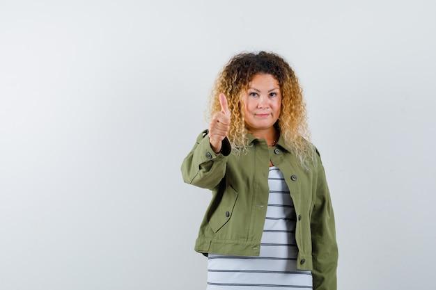 Rijpe vrouw die duim in groen jasje, t-shirt toont en blij, vooraanzicht kijkt.