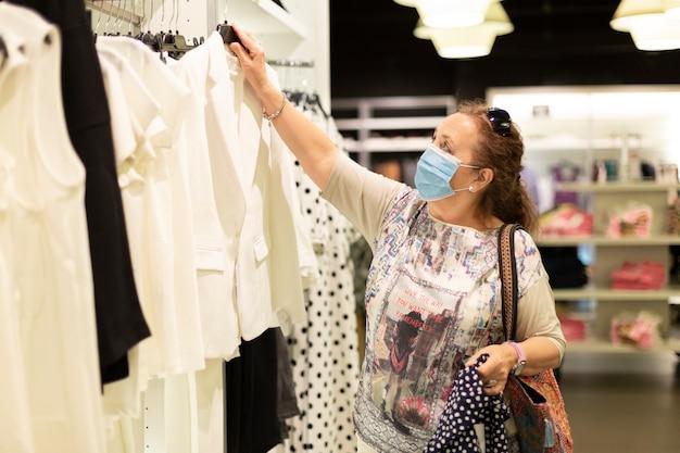 Rijpe vrouw die een gezichtsmasker draagt die kleren in een opslag bekijkt.
