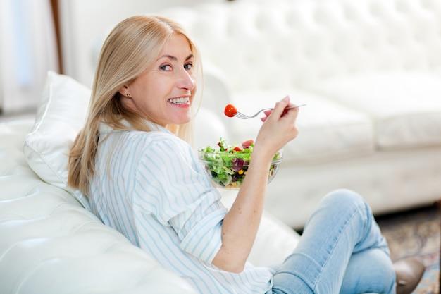 Rijpe vrouw die een gezonde salade op haar bank eet