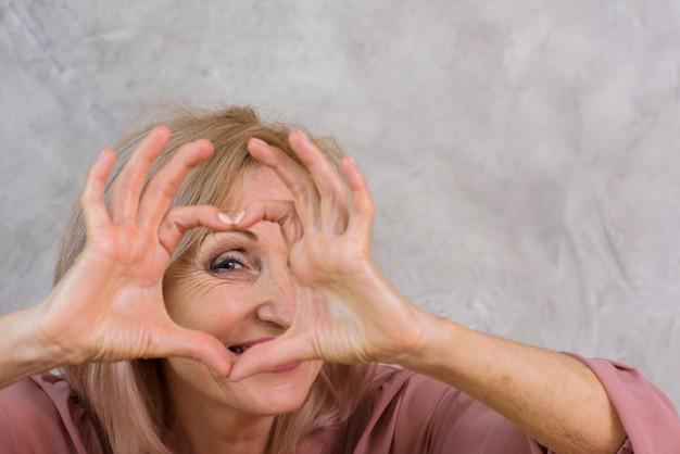 Rijpe vrouw die een hart met haar vingers maakt
