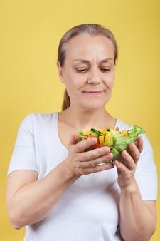 Rijpe vrouw die een plaat van groentesalade houdt