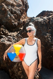 Rijpe vrouw die een strandbal vasthoudt terwijl ze in een zwempak zit