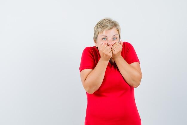 Rijpe vrouw die emotioneel vuisten bijt in rood t-shirt en bang kijkt