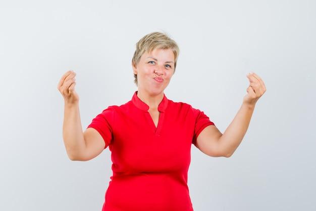 Rijpe vrouw die geldgebaar in rood t-shirt toont en vrolijk kijkt.