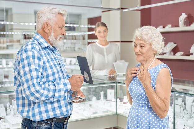 Rijpe vrouw die genoegen van het winkelen bij juwelenopslag neemt
