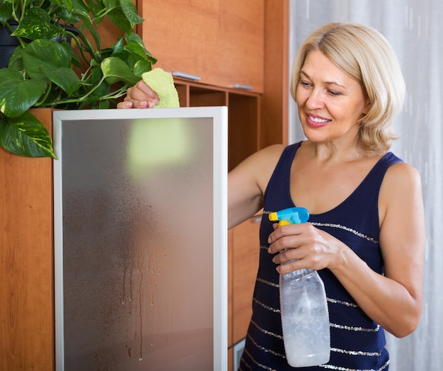Rijpe vrouw die glasdeur schoonmaakt