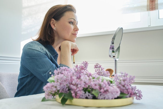 Rijpe vrouw die haar gezicht in de spiegel bekijkt