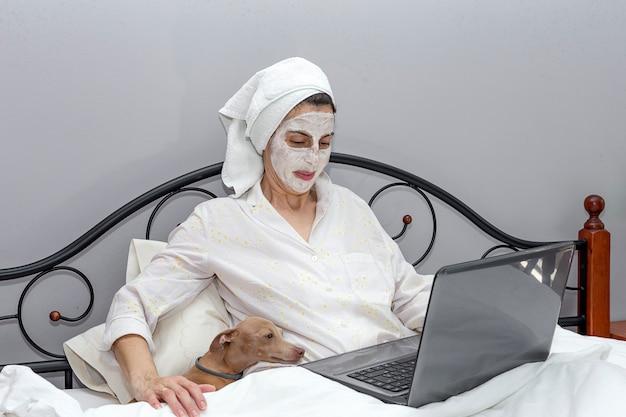 Rijpe vrouw die haar gezicht met een gezichtsmasker in bed met hond behandelen