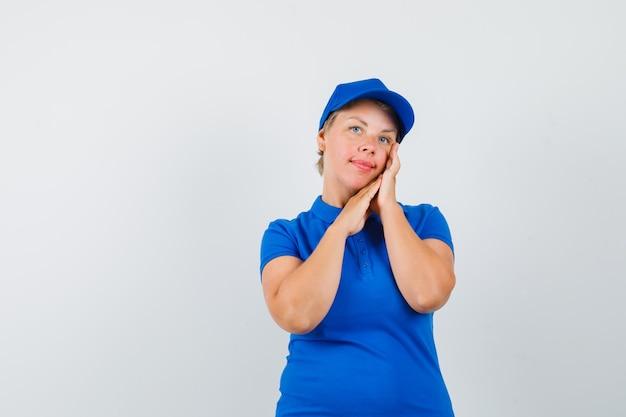 Rijpe vrouw die haar gezichtshuid in blauw t-shirt controleert en elegant kijkt.