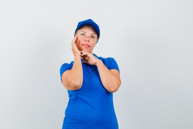 Rijpe vrouw die haar gezichtshuid in blauw t-shirt controleert