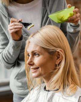 Rijpe vrouw die haar haar thuis door kapper krijgt geverfd