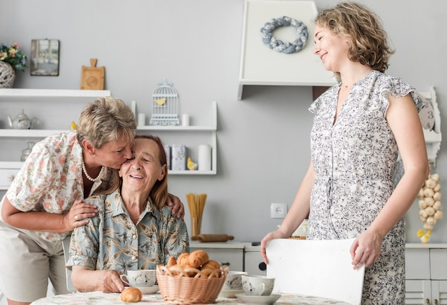 Rijpe vrouw die haar hogere moeder in keuken kust