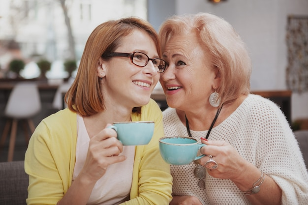 Rijpe vrouw die haar hogere moeder ontmoet bij de koffiewinkel