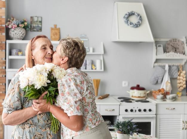 Rijpe vrouw die haar moeder kussen die wit bloemboeket thuis houden