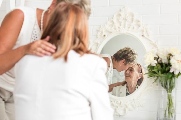 Rijpe vrouw die haar moeder thuis troostend voor spiegel troosten