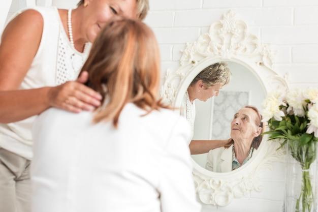 Rijpe vrouw die haar moederzitting voor spiegel bekijkt