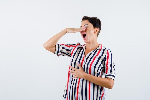 Rijpe vrouw die hand boven de mond houdt, die in gestreepte blouse probeert te niezen en uitgeput, vooraanzicht kijkt.