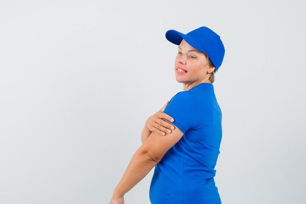 Rijpe vrouw die hand op de andere arm in blauw t-shirt houdt en peinzend kijkt. .