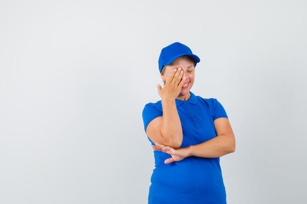 Rijpe vrouw die hand op één oog in blauw t-shirt houdt en vreugdevol kijkt