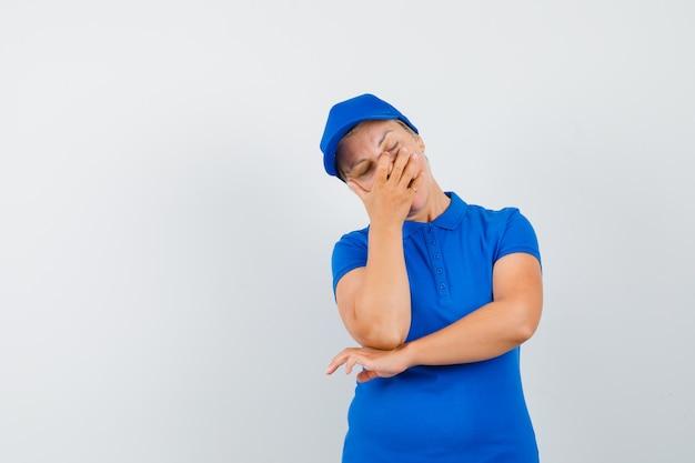 Rijpe vrouw die hand op gezicht in blauw t-shirt houdt en teleurgesteld kijkt.