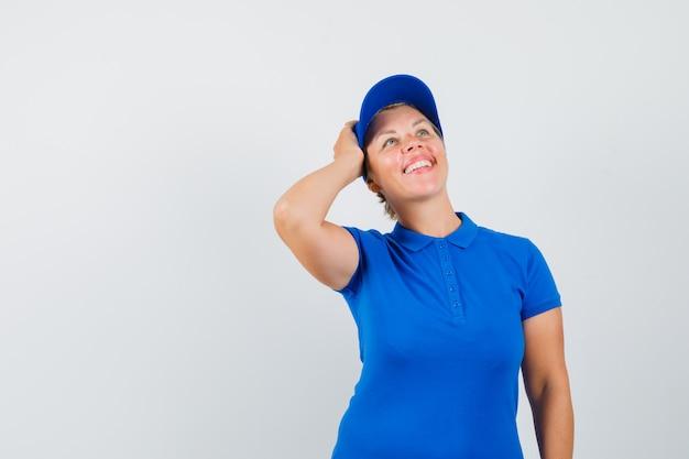 Rijpe vrouw die hand op hoofd in blauw t-shirt houdt en dromerig kijkt.