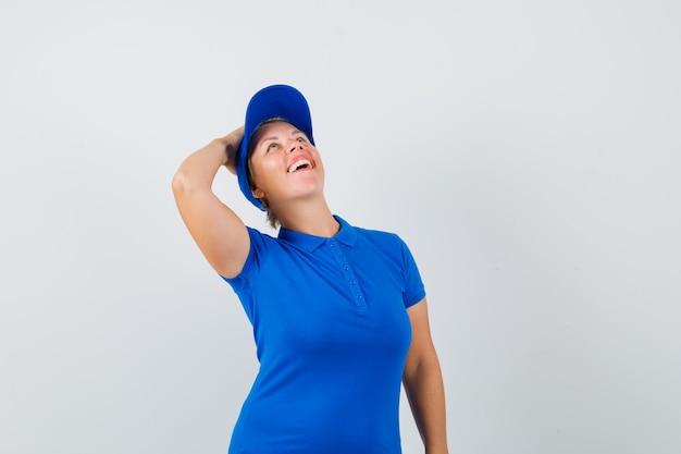 Rijpe vrouw die hand op hoofd in blauw t-shirt houdt en gelukkig kijkt