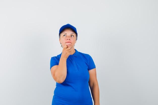 Rijpe vrouw die hand op kin in t-shirt houdt en besluiteloos kijkt