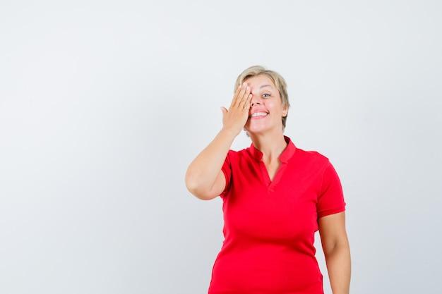 Rijpe vrouw die hand op oog in rood t-shirt houdt en nieuwsgierig kijkt