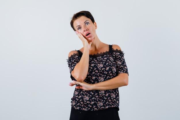 Rijpe vrouw die hand op wang in blouse houdt en in verwarring, vooraanzicht kijkt.