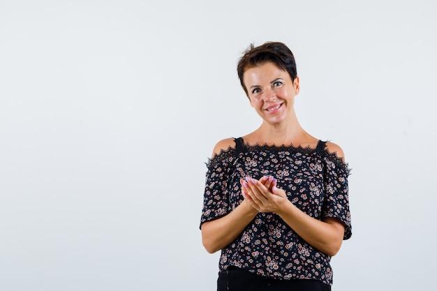 Rijpe vrouw die handen uitrekt als iets in bloemenblouse, zwarte rok vasthoudt en er vrolijk, vooraanzicht uitziet.