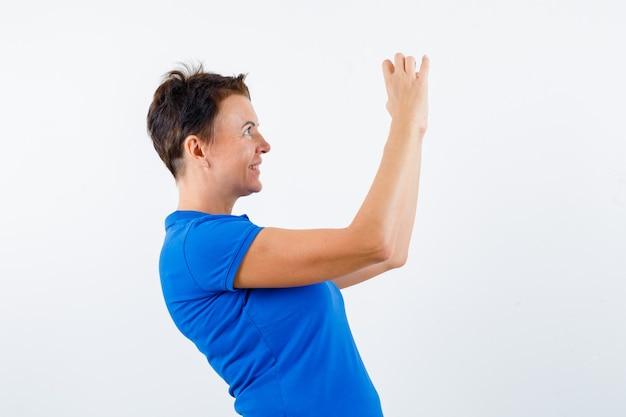 Rijpe vrouw die hartgebaar in blauw t-shirt toont en dromerig kijkt.