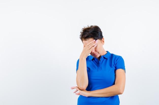 Rijpe vrouw die hoofd in blauw t-shirt buigt en bedroefd kijkt. vooraanzicht.