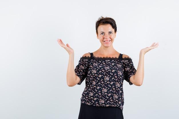 Rijpe vrouw die hulpeloos gebaar in bloemenblouse en zwarte rok toont en vrolijk, vooraanzicht kijkt.