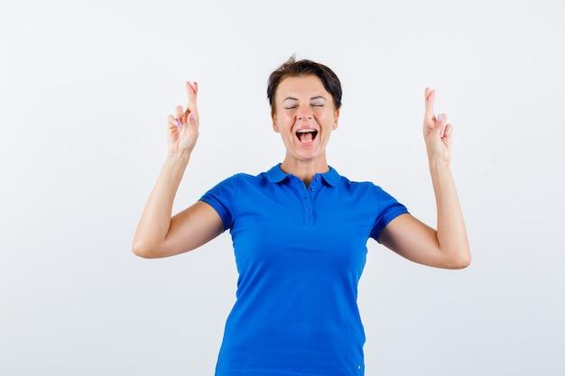 Rijpe vrouw die in blauw t-shirt vingers gekruist houdt en gelukkig, vooraanzicht kijkt.