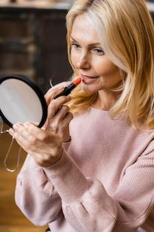 Rijpe vrouw die in de spiegel kijkt terwijl het aantrekken van lippenstift