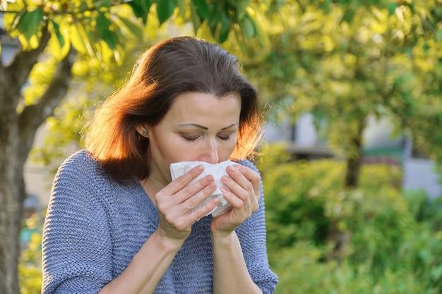 Rijpe vrouw die in zakdoek niest, allergie voor stuifmeel, verkoudheid