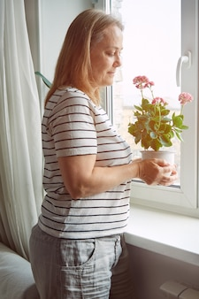 Rijpe vrouw die kamerplant thuis behandelt