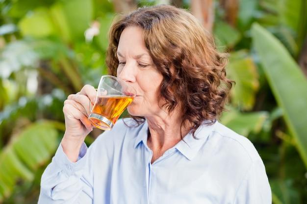 Rijpe vrouw die kruidenthee drinkt
