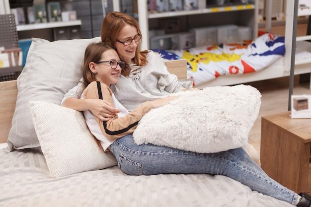 Rijpe vrouw die lacht, haar tienerdochter knuffelt, die samen op een nieuw bed bij meubelwinkel zit