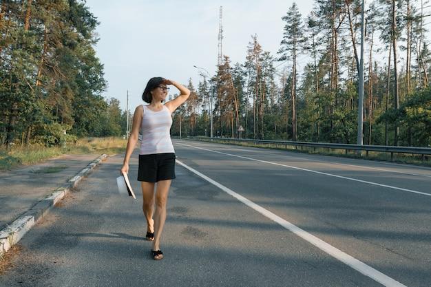 Rijpe vrouw die langs de weg loopt, die de weg bekijkt