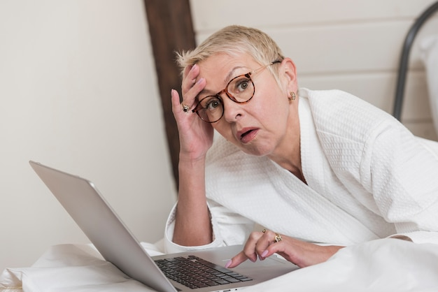 Rijpe vrouw die laptop in bed met behulp van