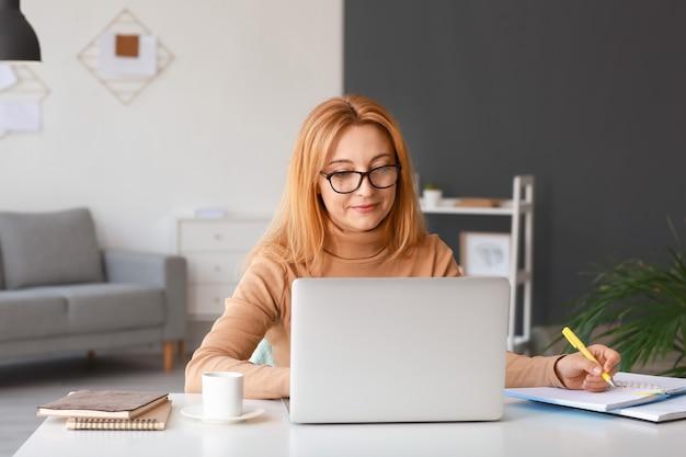 Rijpe vrouw die laptop met behulp van om thuis online te leren