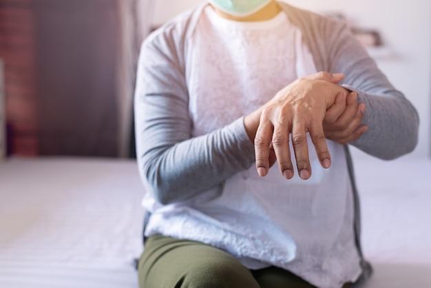 Rijpe vrouw die lijdt aan symptomen van de ziekte van parkinson bij de hand