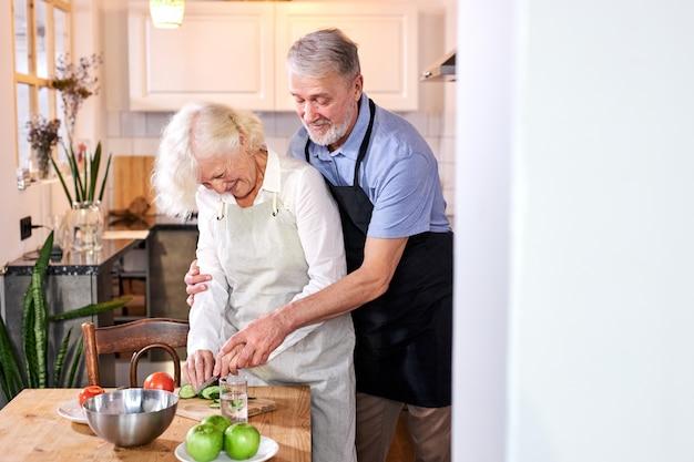 Rijpe vrouw die maaltijd bereidt, haar man helpt haar van rug, groenten snijden