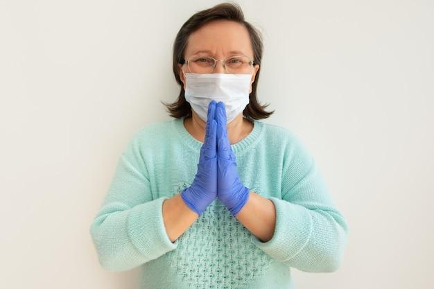 Rijpe vrouw die medisch masker en handschoenen draagt