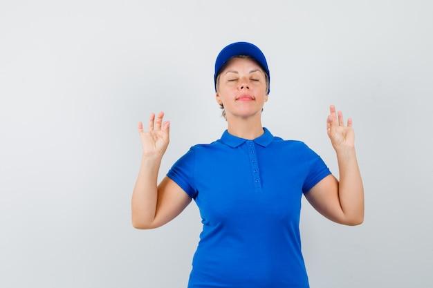 Rijpe vrouw die meditatie met gesloten ogen in blauw t-shirt doet en vredig kijkt