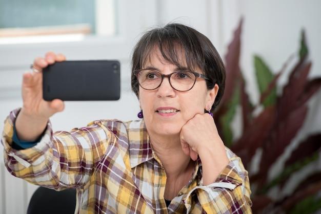 Rijpe vrouw die met gecontroleerd overhemd selfie maakt