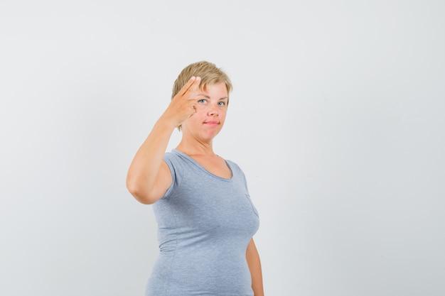 Rijpe vrouw die met hand en vingers in grijs t-shirt gebaart en zelfverzekerd kijkt.